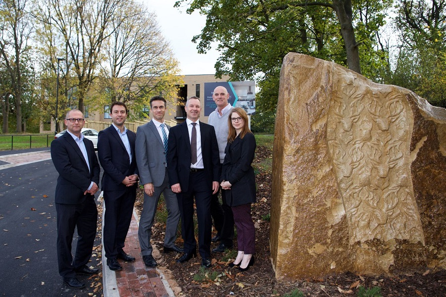 Business people next to community artwork monolith at Sheffield apartment block