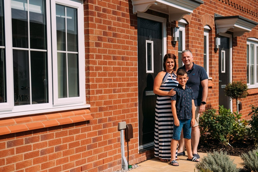 Mother, Father and Son smiling on doorstep of a house