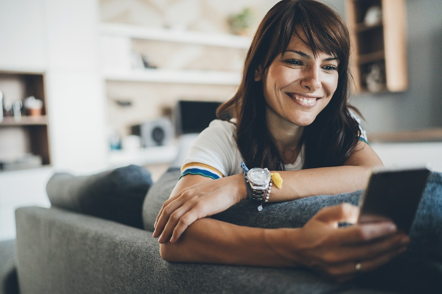 woman smiling at phone on the sofa